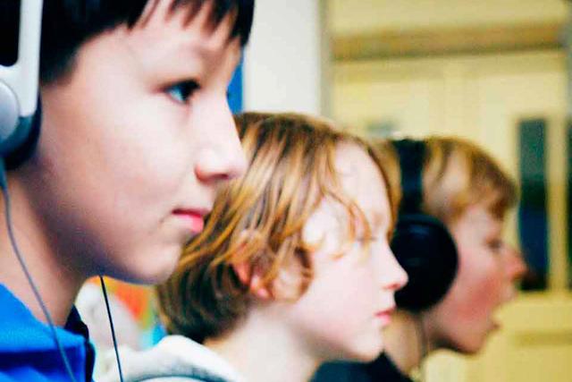 Kinderen zitten met koptelefoon op