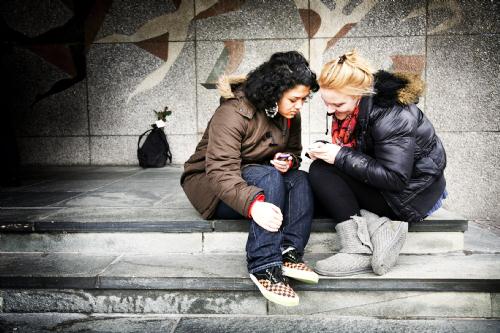 2 jongeren zitten op een trap en kijken naar een telefoon