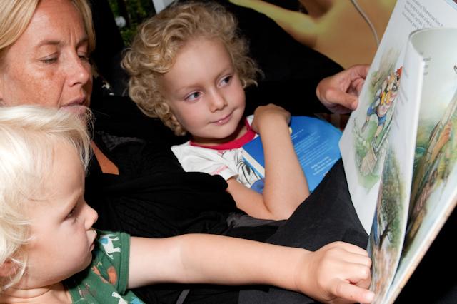 Foto: Twee kinderen worden voorgelezen door een ouder.