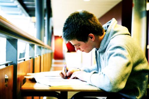 Een tiener maakt huiswerk aan een bureau in de bibliotheek