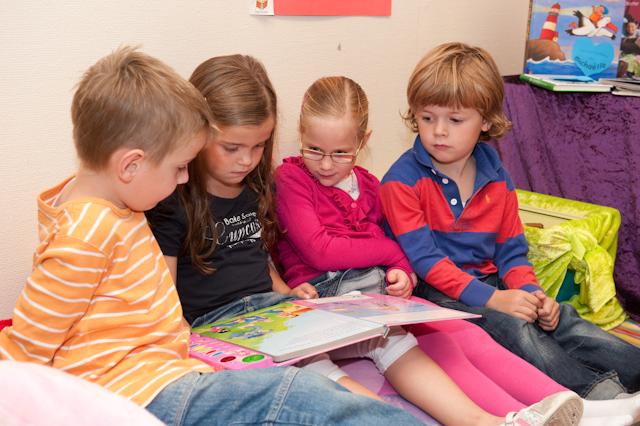 4 kinderen lezen samen een boek