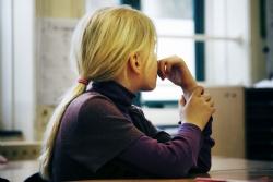 Meisje kijkt voor zich uit. Rond 6 jaar oud. Zit in de klas.