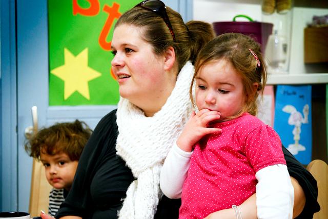 Een moeder met twee kinderen naast zich.