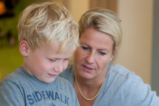 Moeder en zoon kijken samen naar een boekje