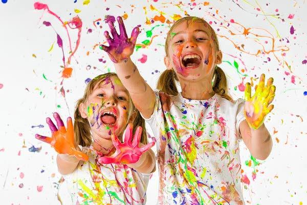 Foto: 2 kinderen die met verf spelen en een high five willen geven