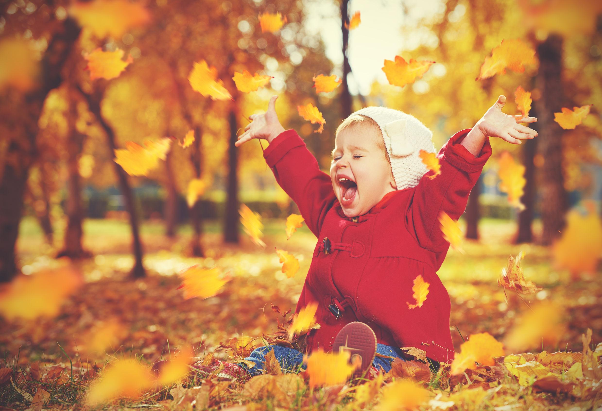 Peuter spelend in bladeren