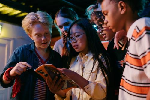 Een divers groepje tieners bekijkt een boekje