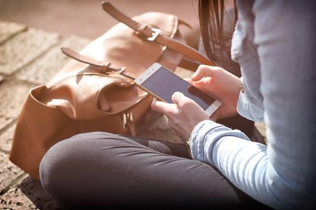 Een jongere zit op de grond met een smartphone in beide handen