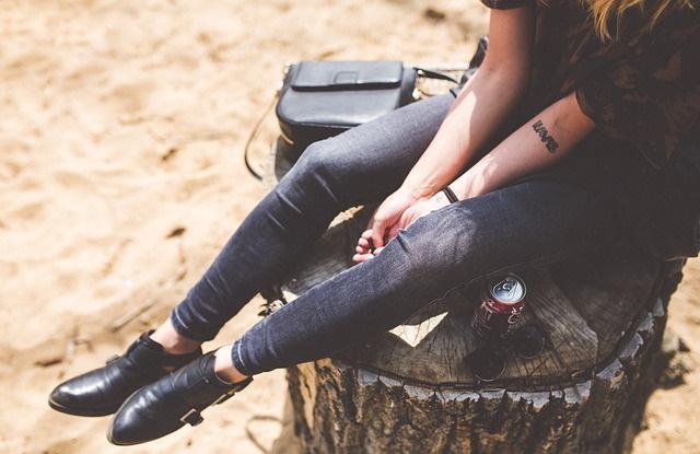 De benen van een meisje in zwart gekleed die op een boomstam zit