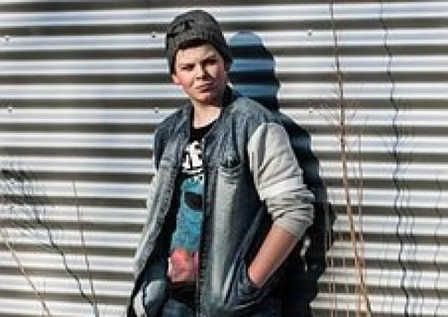 jongen staat tegen een muur