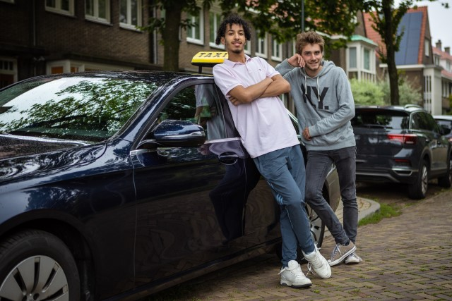 2 jongvolwassenen staan tevreden tegen een taxi aangeleund