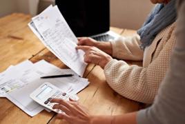 twee mensen aan een tafel achter de laptop met papieren en rekenmachine.