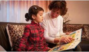vrouw met kind leest boekje op de bank