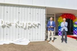 2 mensen van Stichting Leefomgeving Schiphol staan naast de gevel van het nieuwe buurtgebouw De Kuyper. Op de gevel staat de naam De Kuyper.