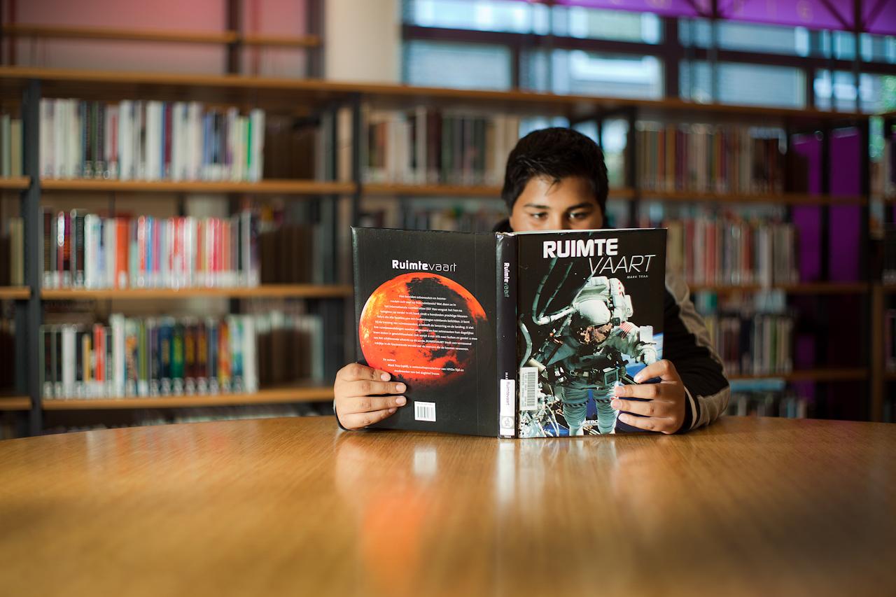 jongen leest boek over ruimtevaart