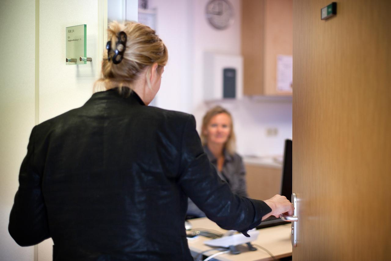 Foto: Vrouw opent deur van spreekkamer