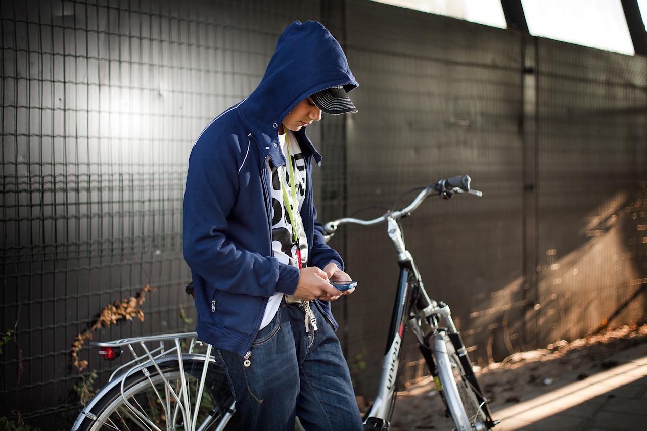 Jongen staand tegen een fiets