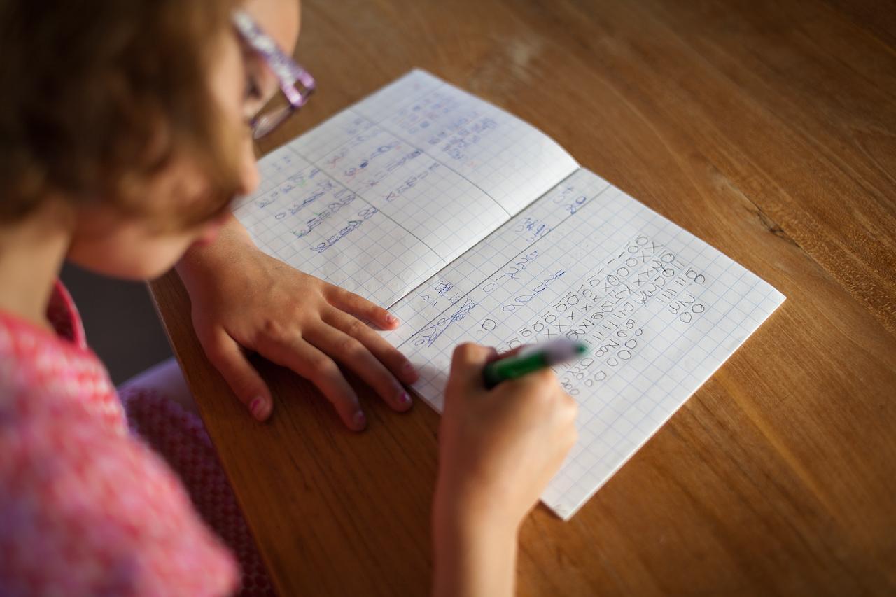Meisje maakt huiswerk aan tafel
