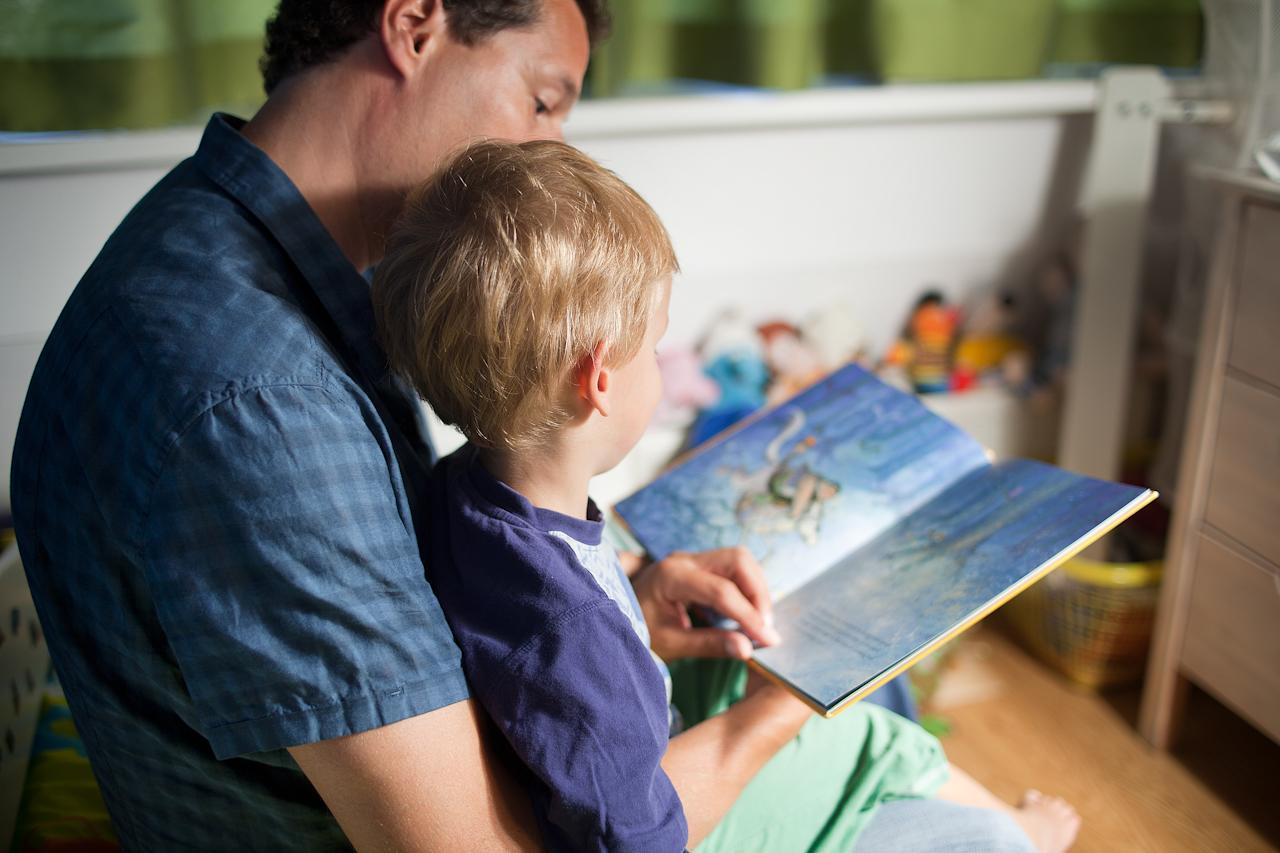 Opvoeder leest boekje met kind
