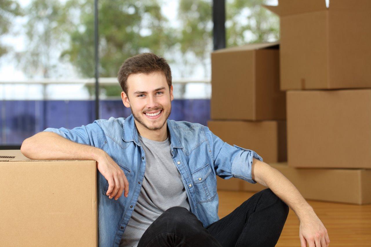 Een jongeman zit tussen op elkaar gestapelde verhuisdozen