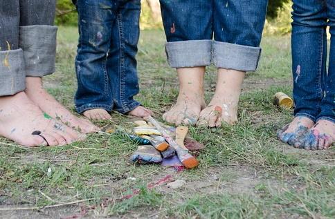 Vier paar blote voeten in het gras met verfkwasten en handschoenen ervoor