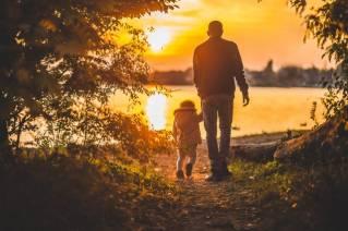 Een vader en kind lopen richting een meeroever