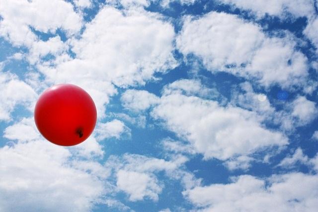 Rode balloon vliegt door de lucht