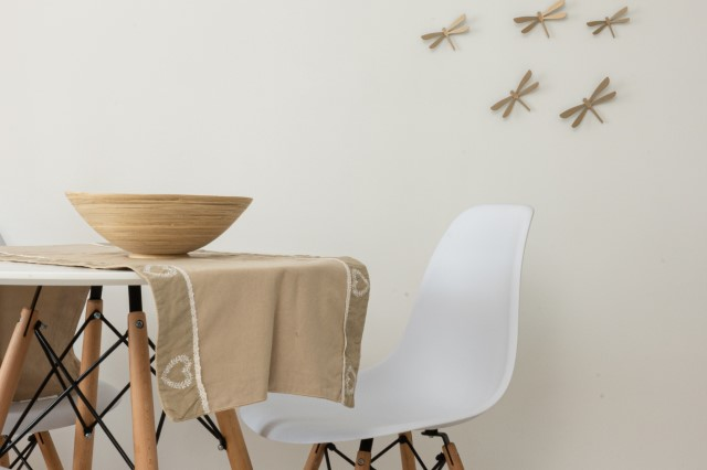 Een kom staat op een tafel, met een stoel naast de tafel