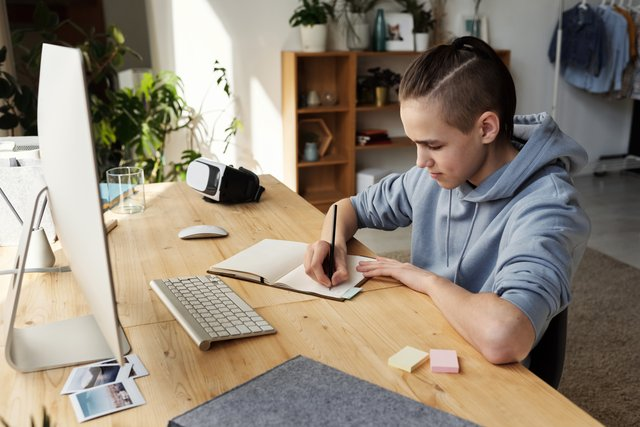 Een tiener met capuchontrui noteert iets in een opschrijfboek terwijl hij achter een computer zit