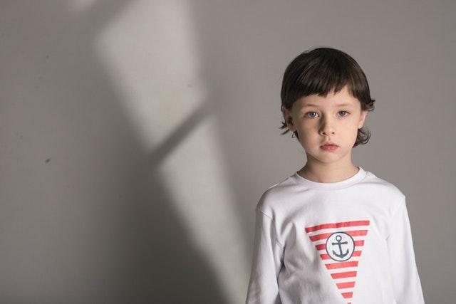 Een kind van rond de 10 jaar met donker haar kijkt recht in de camera