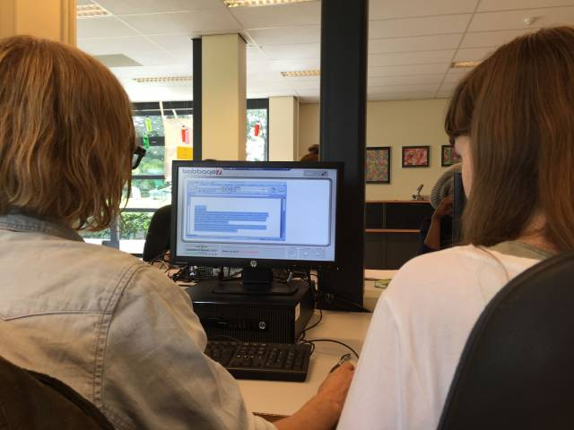 Foto van 2 mensen en een computer