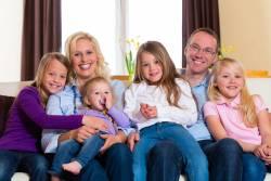 Twee ouders zitten met vier kinderen thuis op de bank