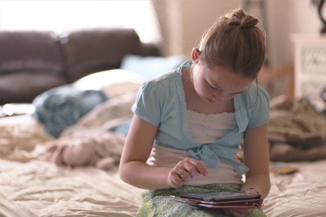 Een meisje zit op een bed terwijl ze een tablet bedient