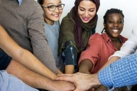 Een groep vrijwilligers staat in een kring en houdt in het midden van de kring handen boven elkaar.