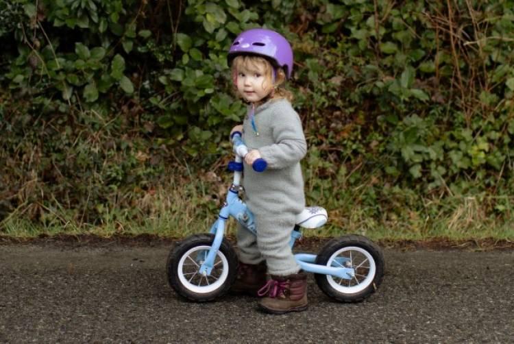 Een peuter gebruikt een loopfiets en draagt een helm