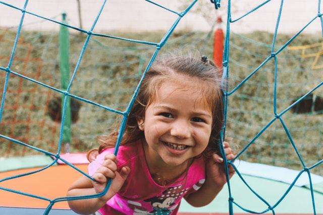 Een kind staat bij een trampoline en kijkt door 2 delen van een net heen