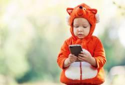 Foto van een kind dat op een telefoon kijkt.