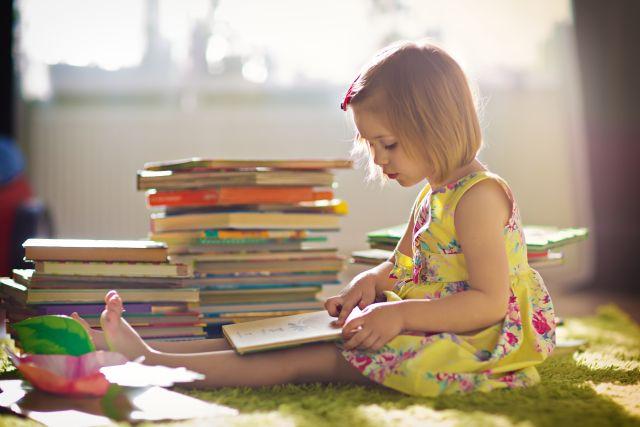 Foto van een kleuter die een boek leest.