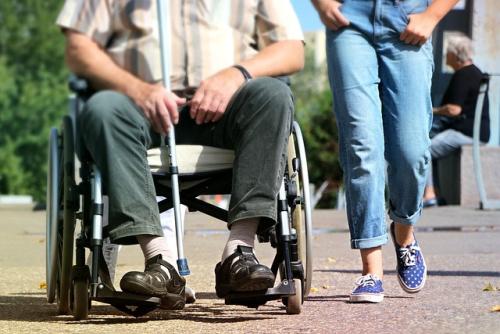 Man in rolstoel en jongere loopt ernaast