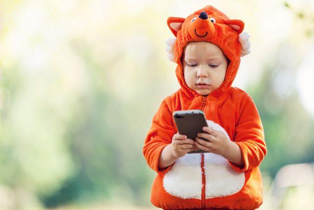 Een peuter in een dieren-verkleedpak houdt een smartphone vast