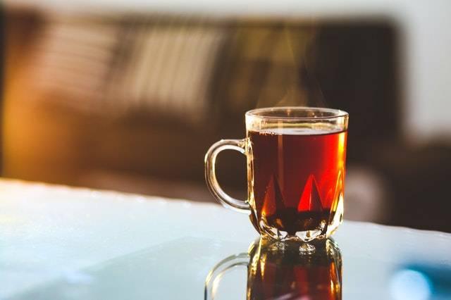 Een kop thee staat bij de rand van een tafel