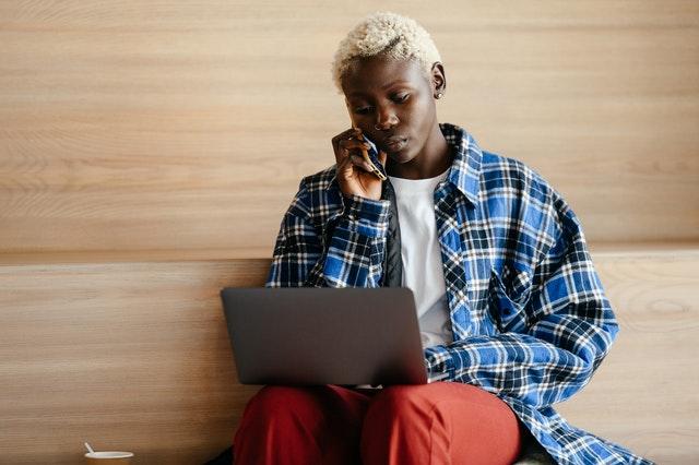 Een jongvolwassene zit met een laptop op schoot en is tegelijkertijd aan het bellen