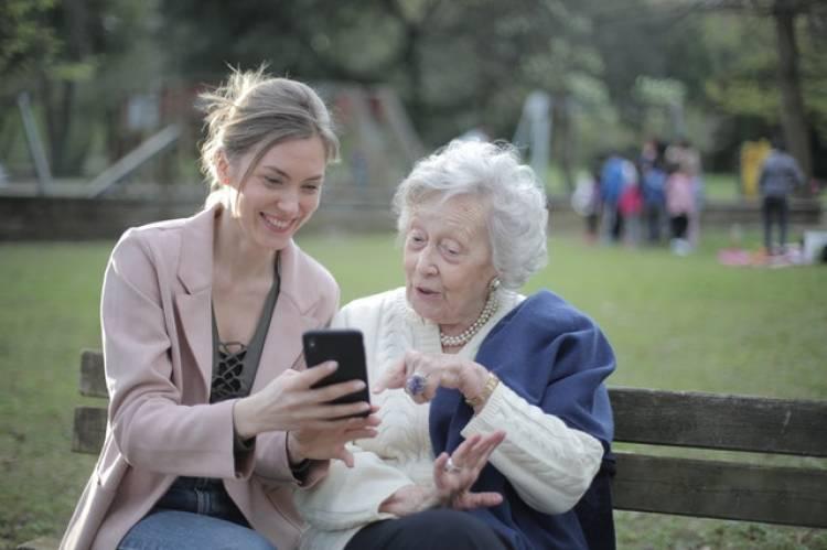 Een jongere vrouw laat aan een oudere vrouw iets zien op haar telefoon, terwijl ze op een bankje zitten