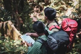 2 jongvolwassenen wandelen in het bos met een rugzak op