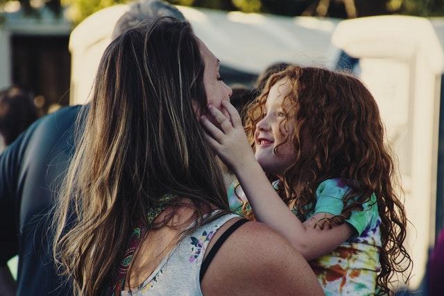 Een moeder houdt haar kleuterkind vast