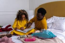 Een vader leest zijn dochter voor op een bed