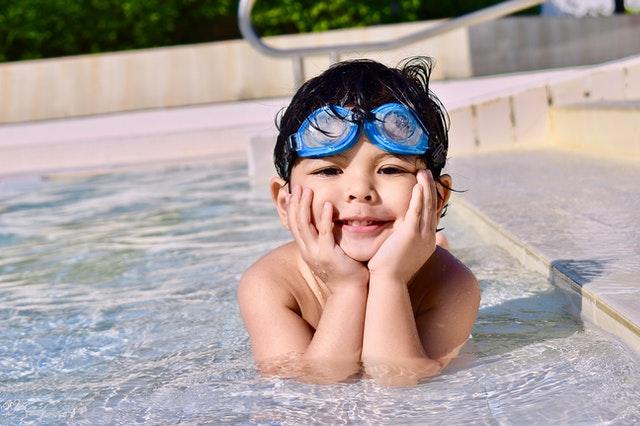 Een kind ligt op zijn buik in een ondiep stuk water in het zwembad