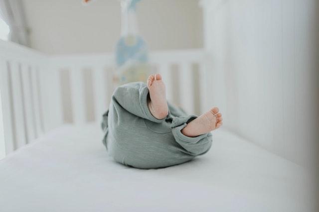 Een baby ligt op zijn rug in een kinderbedje