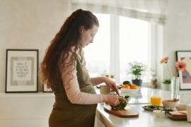 Een zwangere vrouw maakt eten klaar