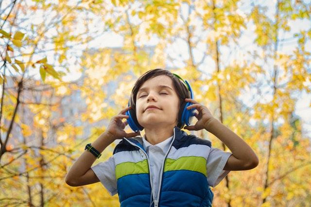Een kind met een koptelefoon op staat in het bos